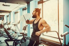 Guy relaxing after workout and hold or drink water from big bottle in gym. Very power athletic bearded guy relaxing after workout and hold or drink water from Stock Photos