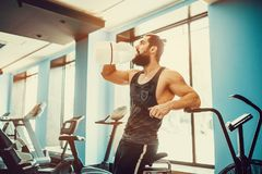 Guy relaxing after workout and hold or drink water from big bottle in gym. Very power athletic bearded guy relaxing after workout and hold or drink water from Royalty Free Stock Images