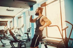 Guy relaxing after workout and hold or drink water from big bottle in gym. Very power athletic bearded guy relaxing after workout and hold or drink water from Stock Photo