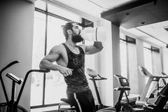 Guy relaxing after workout and hold or drink water from big bottle in gym. Very power athletic bearded guy relaxing after workout and hold or drink water from Stock Images