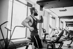 Guy relaxing after workout and hold or drink water from big bottle in gym. Very power athletic bearded guy relaxing after workout and hold or drink water from Royalty Free Stock Photo