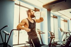 Guy relaxing after workout and hold or drink water from big bottle in gym Royalty Free Stock Images