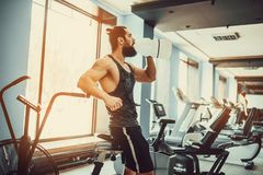 Guy relaxing after workout and hold or drink water from big bottle in gym. Very power athletic bearded guy relaxing after workout and hold or drink water from Royalty Free Stock Image
