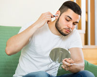 Guy remove hair from his ears Royalty Free Stock Photos