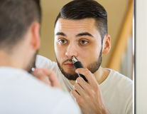 Guy remove hair from his nose Stock Photography