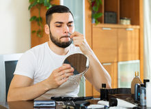 Guy removing nose hair Royalty Free Stock Image