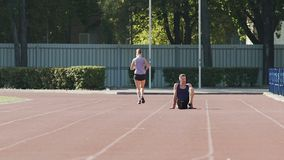 Guy resting on athletic field while girl jogging, sports life, slow-motion. Stock footage stock footage