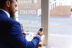 Guy resting in a cafe with phone stock photography