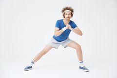 Guy in retro sport suit doing stretching exercises. White background. Sporty retro guy in old fashioned sport suit doing stretching exercises. Isolated on white Royalty Free Stock Image