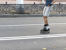 Guy rides on roller skates on the road Royalty Free Stock Photos
