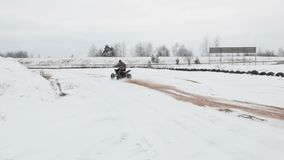 The guy is riding an ATV on a snow-covered road in winter stock footage