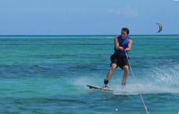 Guy Riding joven un Wakeboard en aguas tropicales Foto de archivo libre de regalías