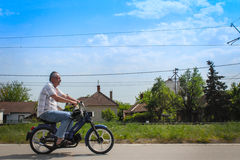 Guy riding motorcycle. Guy riding his motorcycle on a beautiful day on country road. He wears flip-flops and took his safety hamlet of because of the heat Stock Image