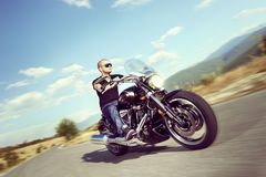Guy riding a motorcycle. On an open road Royalty Free Stock Photo
