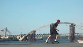 Guy riding skateboard. Skateboarder on bridge background. Best place for skateboarding. Modern youth chooses sport stock video footage