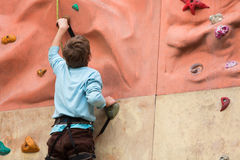 Guy rises to the climbing wall. Stock Images
