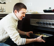 Guy roasting meat in the oven. Smiling guy roasting something in the oven at home kitchen Royalty Free Stock Image