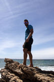 Guy on a rock on the beach. Resting in summer Stock Photography