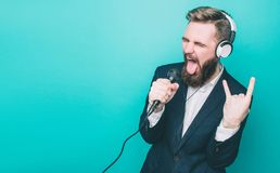 Guy is rocking out. He has the headphones and singing in microphone. Also he is showing the rock symbol with his hand Royalty Free Stock Photos