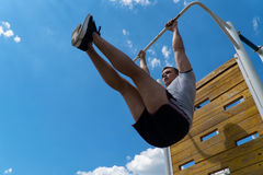 The guy is rocking the press on the horizontal bar. Workout outdoors. Blue sky on blackground Stock Image