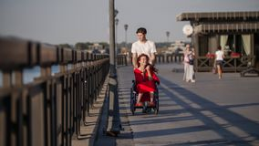 Guy Rolls A Disabled Girl With The Red Hair In A Wheelchair On The Waterfront