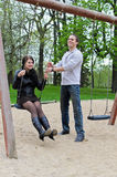 Guy rolls a girl on a swing Royalty Free Stock Photos