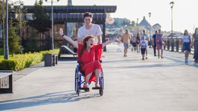 Guy rolls a happy disabled girl in a wheelchair on the waterfront