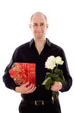 Guy with roses and a gift box. Picture of a young male holding a flower and gift, isolated on white Royalty Free Stock Photography
