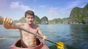 Guy Rows Kayak Actively moreno con salpica contra paisaje marino almacen de video