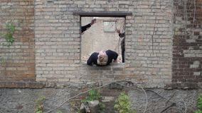 Guy at ruins freedom concepts. Guy is trying to get out through a hole in the wall of the post of the apocalypse on the ground. Young people in black climb into stock footage