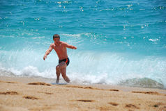 The guy is running away from the waves. Of the Mediterranean sea in Spain Royalty Free Stock Photography