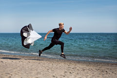 Guy running on beach with parachute. Young man dressed in black uniform running with parachute on beach on sunny day Royalty Free Stock Photography