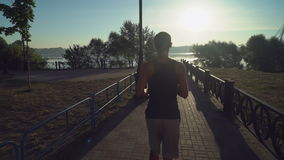 Guy running the camera along the path of the fence near the lake. Jogger runs outdoor at sunrise in summer. Rear back view runner jogging along sports ground stock footage