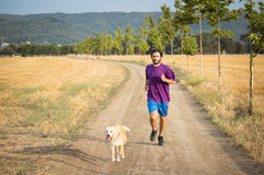 Guy running with a dog Stock Photo