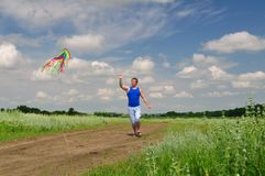 Boy flying a kite in a field stock images