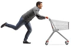 Guy running and pushing an empty shopping cart isolated on white Royalty Free Stock Image