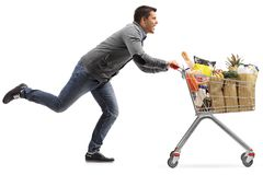 Guy running and pushing a shopping cart filled with groceries Royalty Free Stock Image