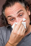 Guy with a runny nose Royalty Free Stock Image