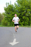 The guy runs along the asphalt road. The athlete runs along the asphalt road, the guy in the white T-shirt in the summer Stock Photography