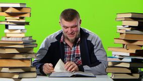 Guy that`s fun reading and leafing through the book. Green screen stock video footage