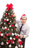 Guy with Santa hat standing by a Christmas tree Royalty Free Stock Photography
