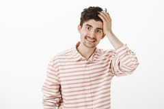 Guy saying sorry, admitting fault. Portrait of ashamed insecure attractive male model with beard and moustache, touching. Hair and smiling awkwardly, being Royalty Free Stock Images