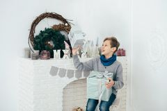 The guy schoolboy sits at the fireplace and holds the box with a gift in his hands. Holiday time. The guy schoolboy sits at the fireplace and holds the box with Stock Image