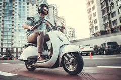 Guy on scooter. Handsome bearded guy in sun glasses and helmet is smiling while riding a scooter Royalty Free Stock Photo