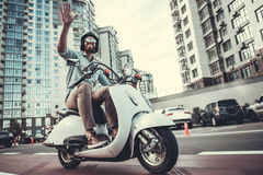 Guy on scooter. Handsome bearded guy in sun glasses and helmet is waving and smiling while riding a scooter Royalty Free Stock Photo