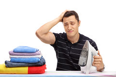 Guy scratching his head and looking at clothes Stock Photos
