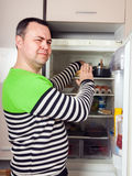 Guy searching for something in refrigerator. Handsome man looking for something in refrigerator at kitchen stock photo