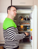 Guy searching for something in refrigerator. Guy looking for something near fridge royalty free stock photos