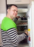 Guy searching for something in refrigerator. Guy looking for something in pan near fridge at home stock images