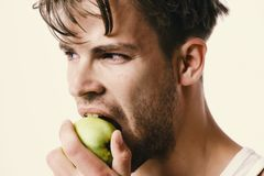 Guy with serious face isolated on light grey background, close up. Man with green apple in his hand bites it. Athlete Royalty Free Stock Image
